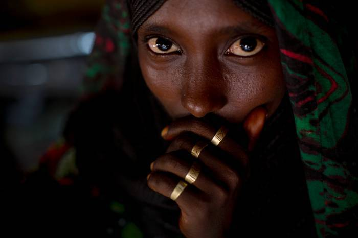 An Afar woman poses for a photograph in her hut in woreda of Geega near Logya. Kate Holt.