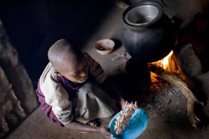Baby Larumbe sifts through beans before cooking them on her family's homestead. Kate Holt.