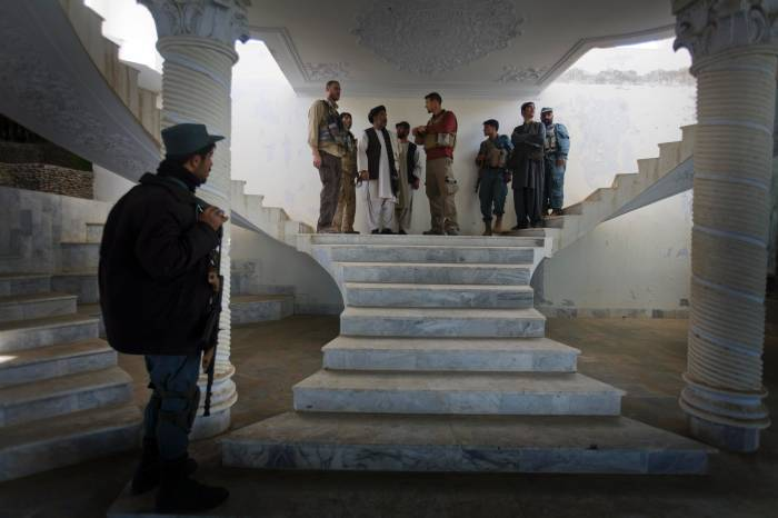 An Afghan Policeman stands guard while Chris Harich, (L) a US State Department Officer, and Kevin Melton (R) from USAID. Kate Holt.