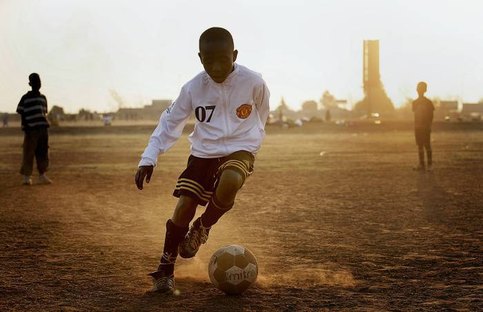 In an African township, Roto Seleke, 11, kicks a ball around in the dirt.. Kate Holt.