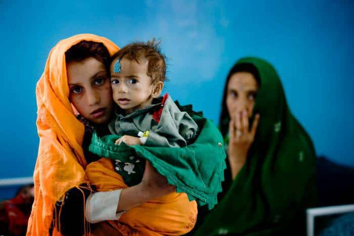A young girl holds her nephew who is suffering from malnutrition at a therapeutic feeding centre. Kate Holt.