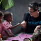 Katy Perry fist-bumps a young boy at Sahavola pre school in Analanjirofo. Kate Holt.