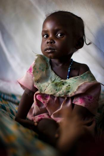 A young girl sits under a mosquito net at a therapeutic feeding centre. Kate Holt.
