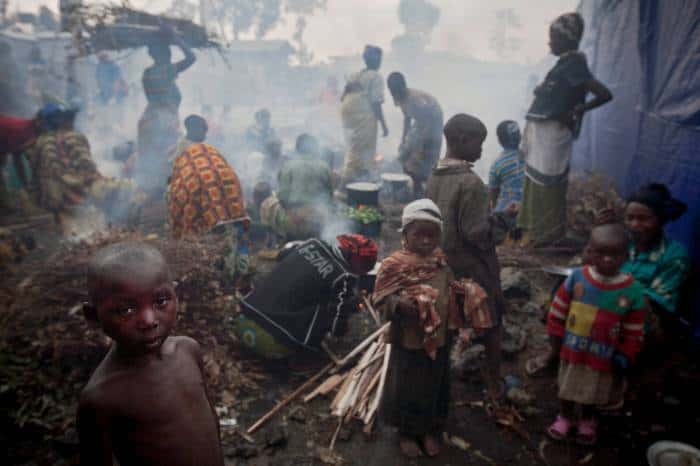 Families displaced by recent fighting between M23 rebels and Congolese Government soldiers try to cook their daily meal. Kate Holt.