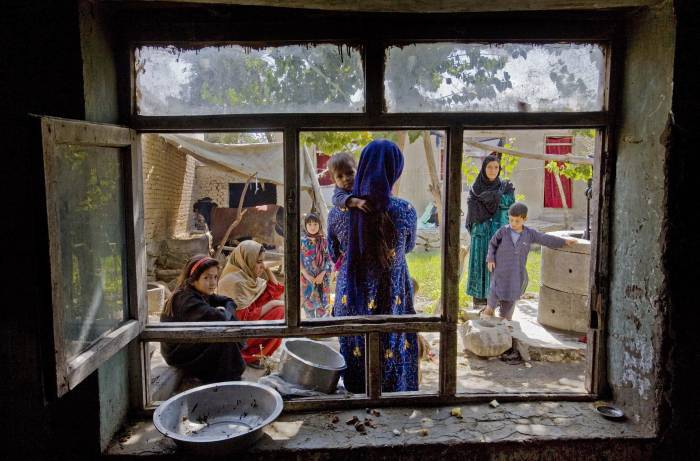 Halima, her children and other women sit outside their houses that they share in Sector 7. Kate Holt.