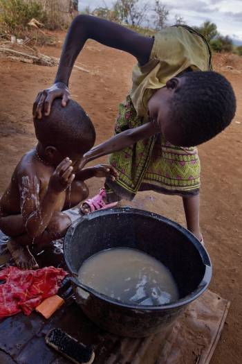 Maua Juma washes her little brother outside their family's house in the town of Makuyuni. Kate Holt.