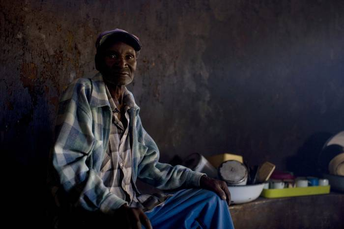 Smao Kemobo, a resident of Melford Farm elderly people's home sits for a photograph in Harare. Kate Holt.