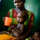 A mother who is a refugee from Darfur tries to feed her malnourished child watched on by her daughter. Kate Holt.