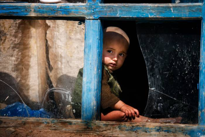 A son of Samajan, who has four children, poses for a portrait in a broken window at the family's home. Kate Holt.
