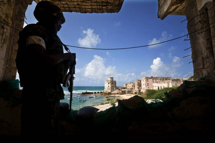 An AMISOM soldier keeps watch over the Old Seaport from a position in the derelict Aruba Hotel in Mogadishu. Kate Holt.