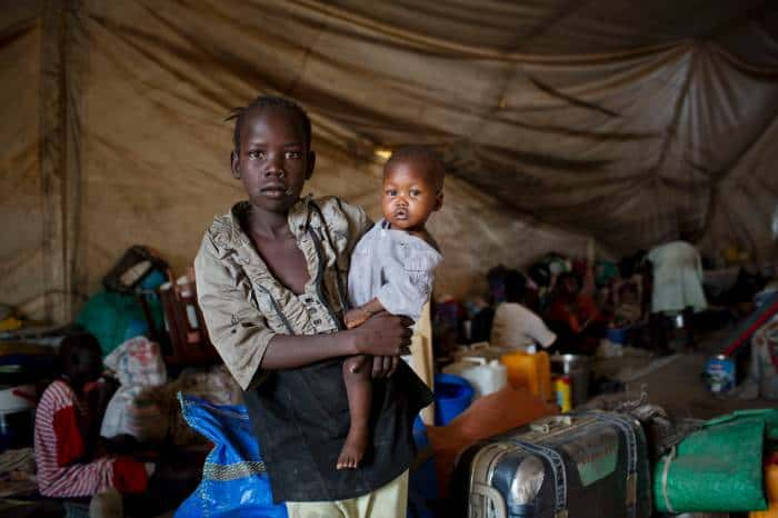 A young girl, displaced by recent fighting, holds her baby brother in a tent. Kate Holt.