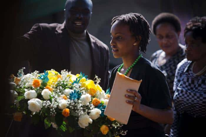 A mourner carries a wreath at the burial of President Kenyatta's nephew Mbugua Mwangi. Kate Holt.