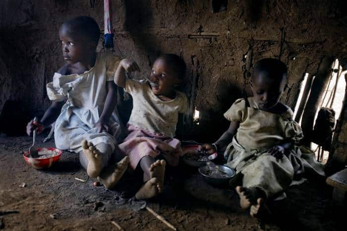 Neema Moshia and two of her siblings sit to eat their daily meal in their mother's kitchen. Kate Holt.