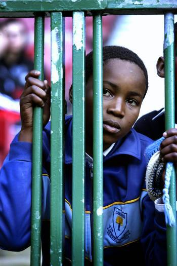 A young Manchester United fan watches through the barricade at a training practise of the team. Kate Holt.