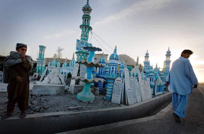 A boy stands next to an outdoor shop selling plaster cast minarets in Kandahar. Kate Holt.