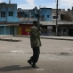 An armed policeman patrols a deserted market in Nakuru town after a day of intense rioting. Kate Holt.