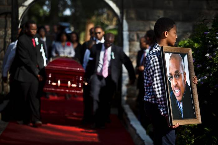 A family member carries a photograph of President Kenyatta's nephew Mbugua Mwangi. Kate Holt.