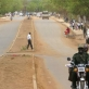 Two men ride on a motorbike drive down a newly tarmaced road in Juba. Kate Holt.