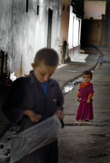 A young girls stands in an alleyway behind her brother who is holding a kite in Sector 7 of Kabul. Kate Holt.