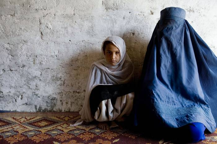 A young girl waits with her mother to receive a polio vaccination. Kate Holt.