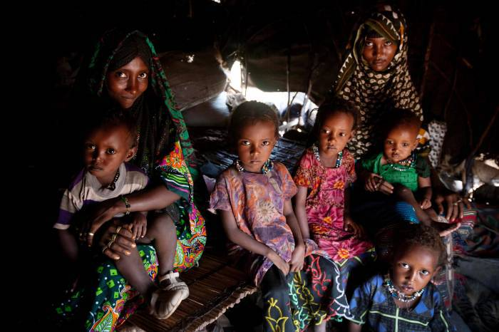 Afar women and their children pose for a photograph in their home in their community of Geega. Kate Holt.