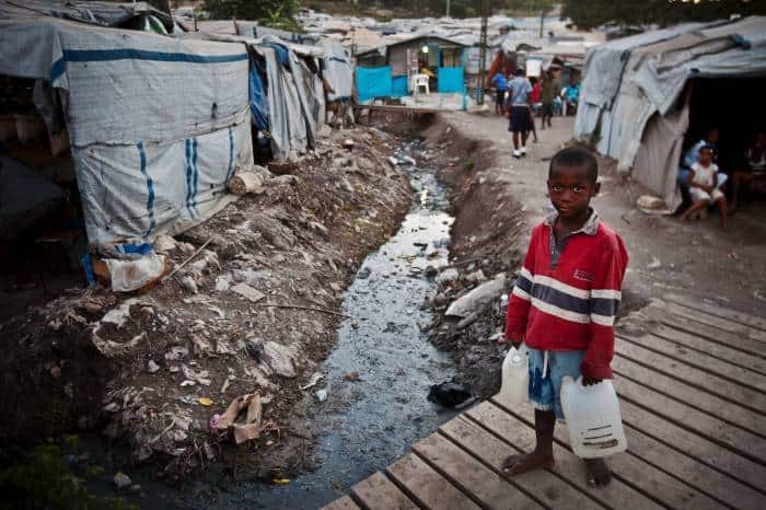 A young boy carries water he has just collected from the stream in a camp for people displaced by the earthquake in Port au Prince. Kate Holt.