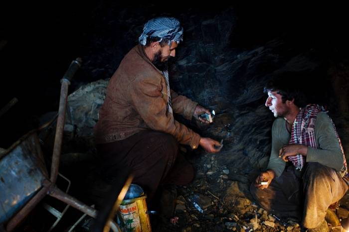Two emerald miners sit in the entrance to a mining tunnel. Kate Holt.