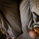 A mother cradles her malnourished child in her lap at a feeding centre that is supported by UNICEF. Kate Holt.