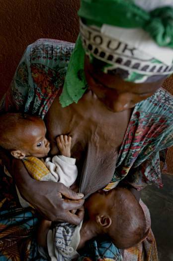 A woman tries to breast feed her two young twins who are suffering from malnutrition. Kate Holt.
