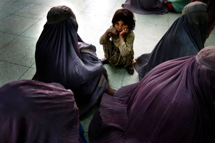 Women cover themselves in burqas as they wait in the maternity ward of Mirwais Hospital. Kate Holt.