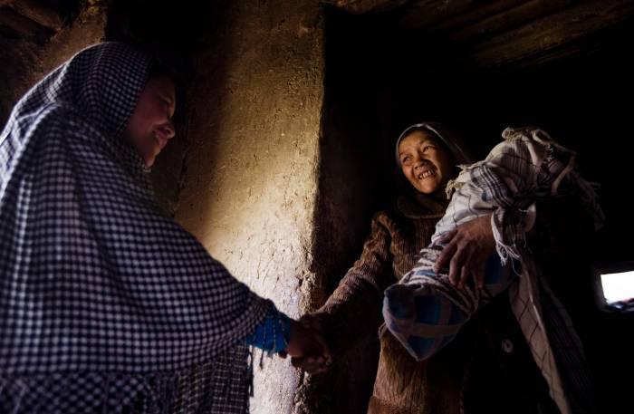 Sadiqa hold her baby Soraya, and shakes hands with Sadiqa Hosseini. Kate Holt.