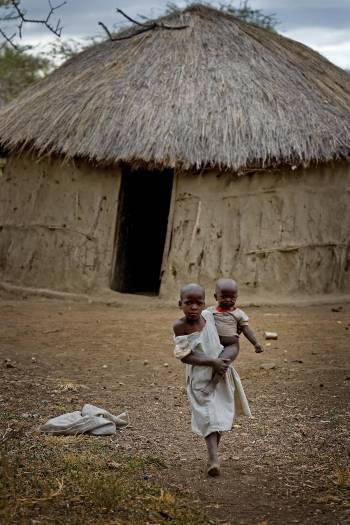 Neema Moshi carries her little brother Godfrey towards her house in the town of Makuyuni. Kate Holt.