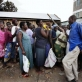 A man waves a stick at women who are queuing for food at a food distribution point in Kisumu. Kate Holt.