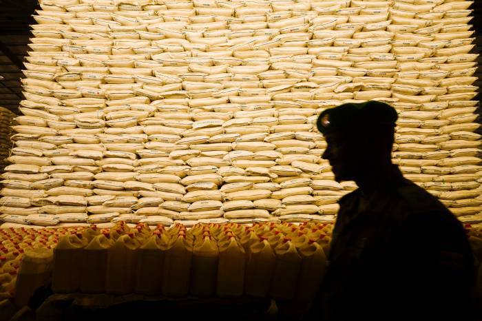 An AMISOM soldier walks past stacked grains sacks in a warehouse at the Seaport in Mogadishu. Kate Holt.