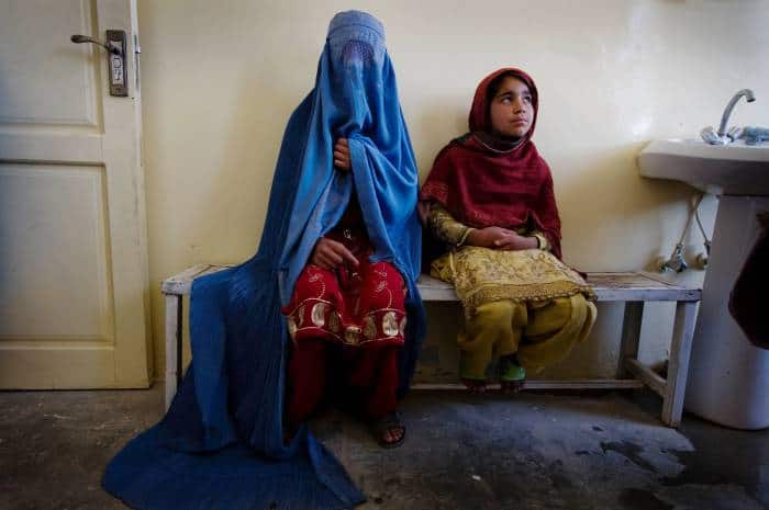 A 14 year old girl, who is about to be married, waits to have a tetanus injection. Kate Holt.