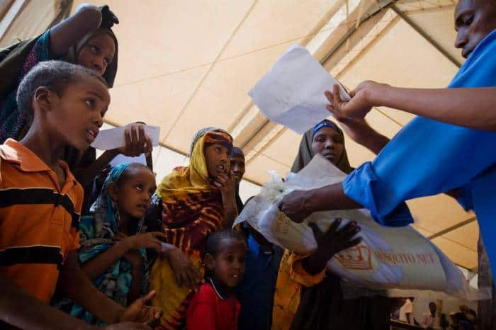 Newly arrived refugees from Somalia receive mosquito nets when they arrive at IFO camp. Kate Holt.