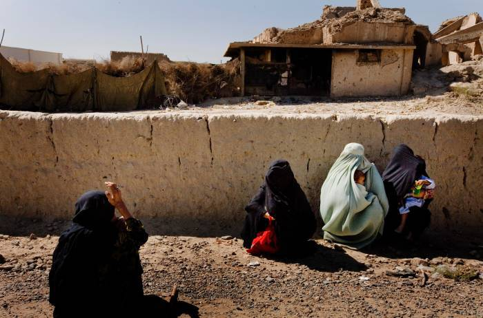 Women in burkas wait with their children to attend a health clinic. Kate Holt.