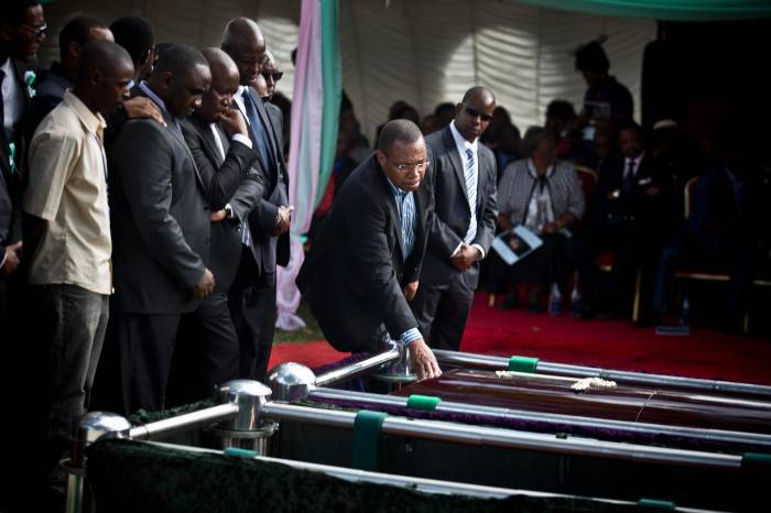 Mourners gather around the coffins of President Kenyatta's nephew Mbugua Mwangi and his fiancee. Kate Holt.