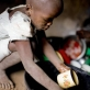 Neema Moshi washes up the dishes for her family after eating in the town of Makuyuni. Kate Holt.