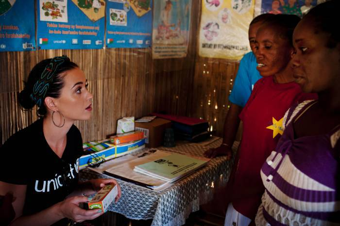 Katy Perry asks a question to a community health worker about the benefits of a supplementary food powder. Kate Holt.