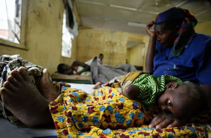 A woman cradles her child who is suffering from cholera in the general hospital. Kate Holt.
