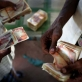 A Somali businessman counts out money for a passengers fare to Yemen. Kate Holt.