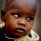 Simineti, who is two years old, is held by his mother on their homestead in Oldonyo. Kate Holt.