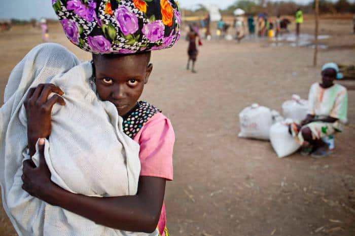 A young girl holding her baby sister displaced by recent fighting between rebel soldiers. Kate Holt.