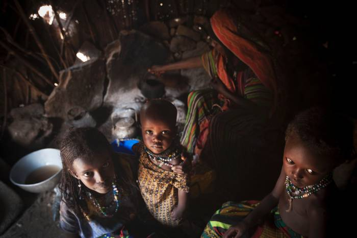 Afar women and their children pose for a photograph in their home in the community of Geega. Kate Holt.