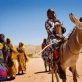 Women arrive by donkey and with their children to a community mobilisation meeting. Kate Holt.
