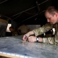 Captain Ian Wilson of 1 Scots sticks labels on a map indicating where IED's had been found. Kate Holt.