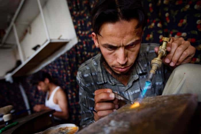 Workers make jewellery in the workshop of Javed Noori in Kabul. Kate Holt.