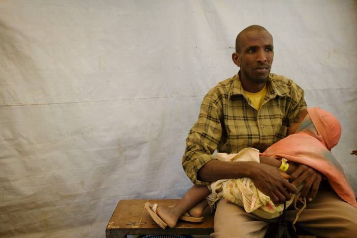 A man waits with his sick daughter while he is registered at IFO camp. Kate Holt.
