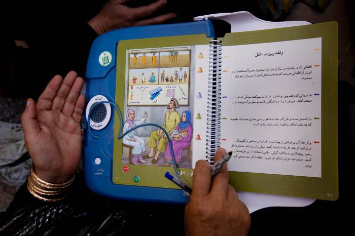 Alia Walezada a CBE (Community Based Educator) uses a talking book to describe aspects of primary and child health care. Kate Holt.